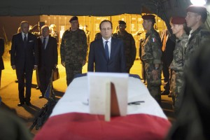 French President Hollande pays tribute near a flag-draped coffin bearing one of two French soldiers who was killed overnight, in Bangui