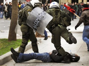 A riot policeman kicks a protester during clashes in Athens