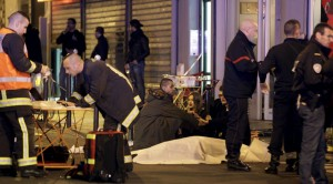General view of the scene that shows rescue services personnel working near the covered bodies outside a restaurant following a shooting incident in Paris